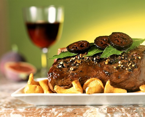 Roast venison with figs and chanterelles; Red wine glass