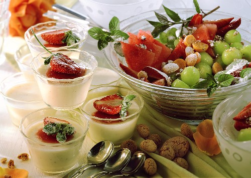 Panna cotta in small bowls, fruit salad and amaretti