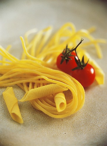 Still life with pasta (garganelli, spaghetti) and tomatoes