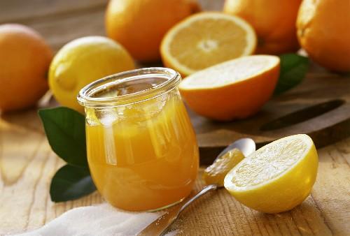Orange jelly with lemons in jar; fresh citrus fruits