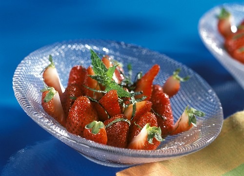 Marinated strawberries with fresh mint in glass bowl