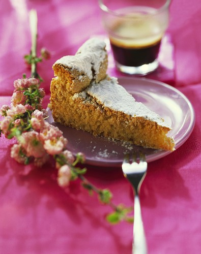 Piece of almond cake with icing sugar; pink flowers; coffee