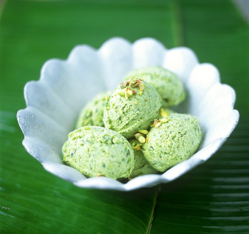Pistachio ice cream in white bowl on banana leaf