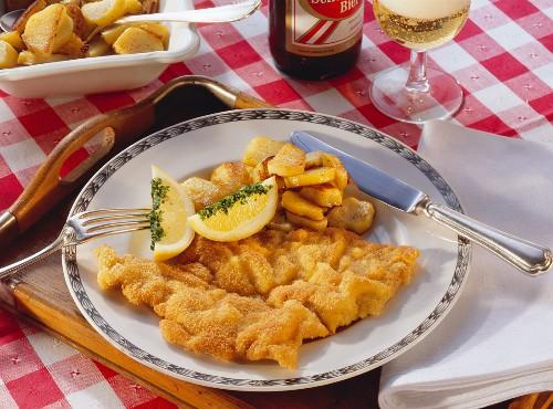 Wiener Schnitzel with lemon wedge & fried potatoes