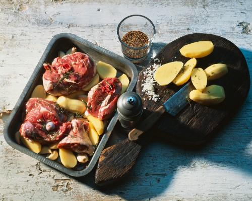 Preparing lamb shank with potatoes in roasting dish