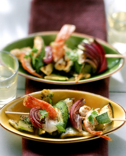 Shrimp kebab with courgettes and onions on artichokes