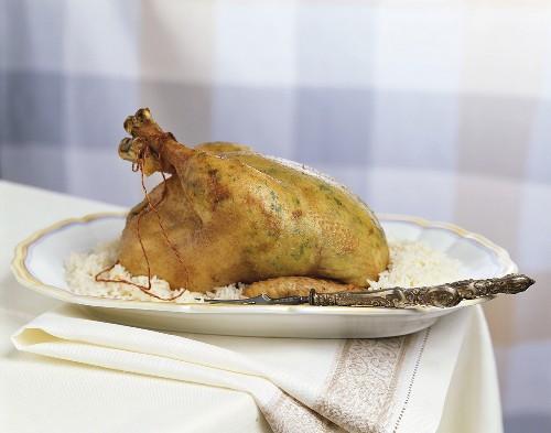 Roast chicken stuffed under the skin, with rice