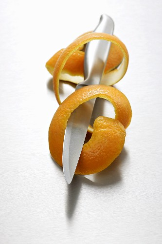 Spiral of orange peel with knife