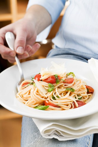 Person eating spaghetti with tomatoes