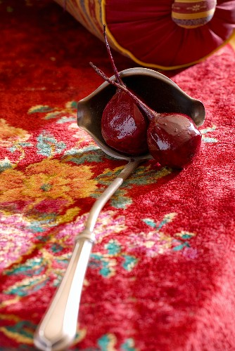 Two cooked beetroots in ladle on carpet