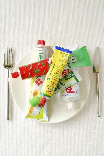 Various tubes (tomato puree, mayonnaise etc.) on plate