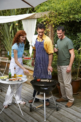 Two men and a woman barbecuing food in garden