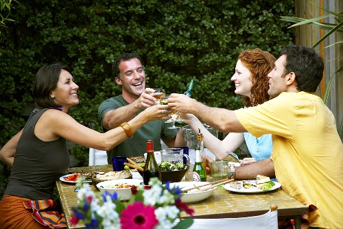 People clinking wine glasses at party in garden