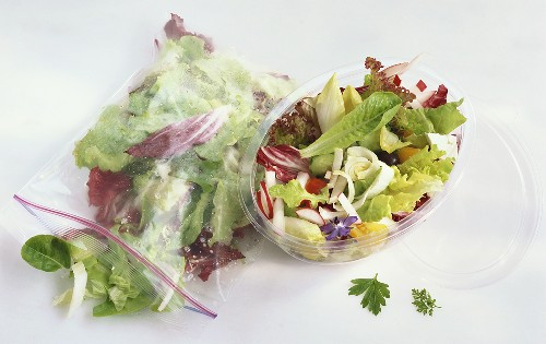 Mixed salad in plastic food bag and plastic container