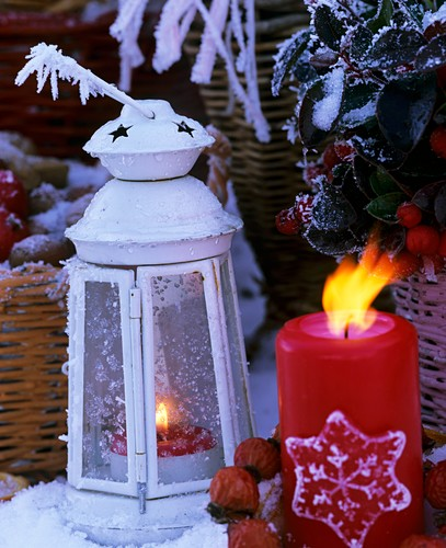 White lantern with candle in snow