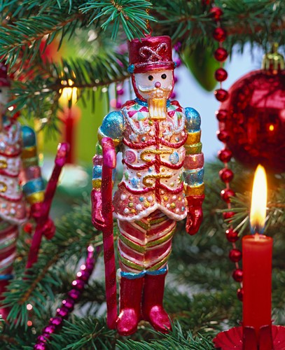 Nutcracker and burning candle on Christmas tree