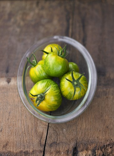 Several tomatoes, variety 'Green Zebra', in glass dish