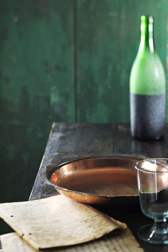Copper dish, bottle of wine and old exercise books