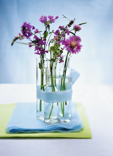 Purple flowers in small bottles (table decoration)