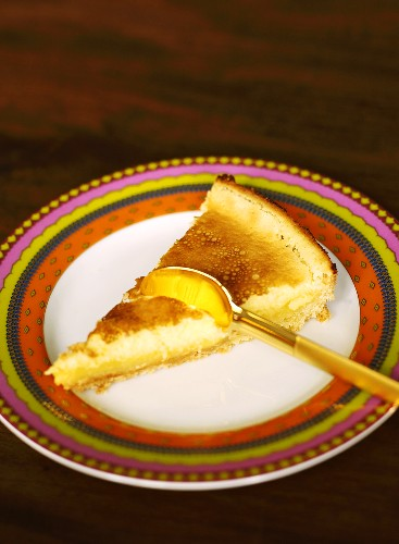 Piece of lemon tart on plate with spoon