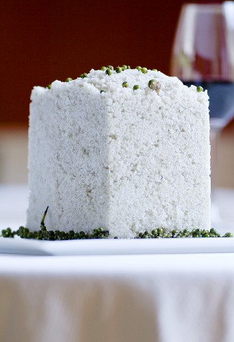 Cube of salt with green peppercorns