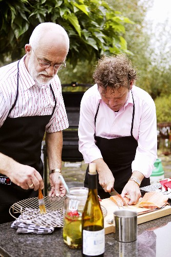 Two men preparing salmon for barbeque