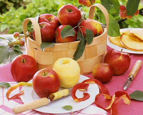 Apples in woodchip basket and on plate with apple corer
