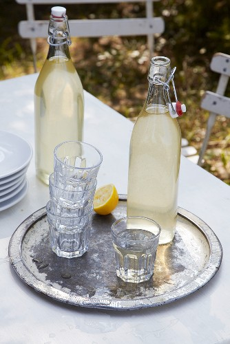 Two bottles of lemonade and glasses on a tray