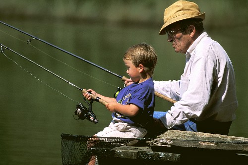 A grandfather and grandson fishing at a lake