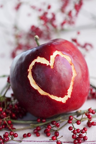 Red apple with a heart scratched in the skin