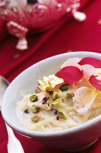 Pasta dessert with pistachios, gold leaf and rose petals