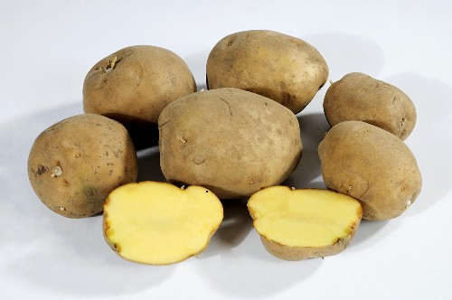 Several potatoes (variety 'Auralia'), whole and halved