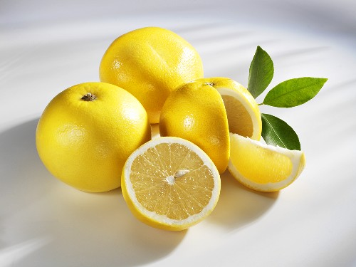 Several yellow grapefruits (whole, halved and a wedge)