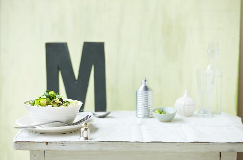 Pasta with courgettes and lime, letter M in background