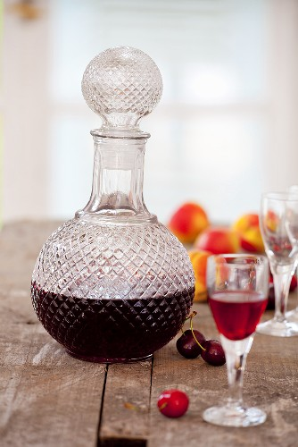 Homemade cherry and apricot liqueur in a carafe and a glass
