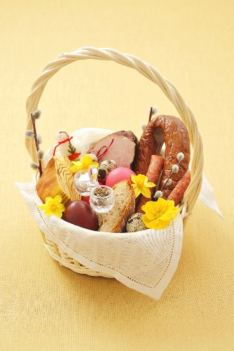 Bread, eggs, sausage, ham and pastries in Easter basket
