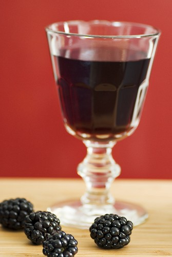 Glass of red wine with subtle blackberry note, fresh blackberries