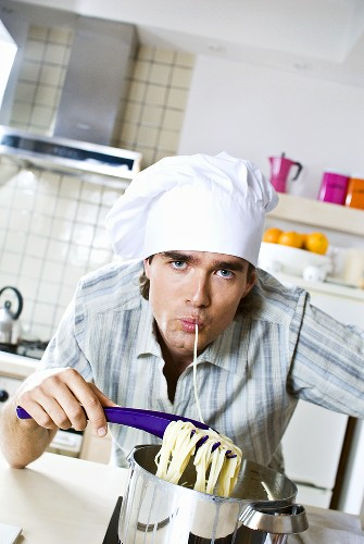 Man in chef's hat eating spaghetti out of pan