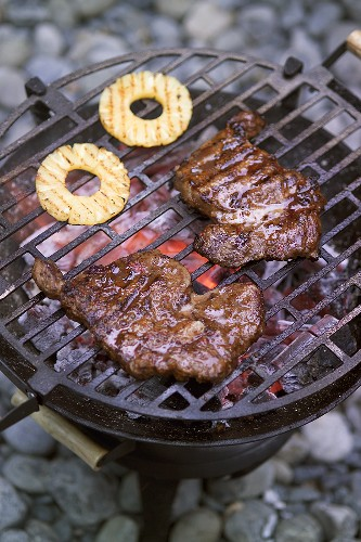 Beef steaks and pineapple slices on the barbecue