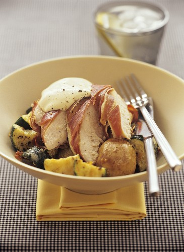 Chicken breast fillet wrapped in ham on vegetables