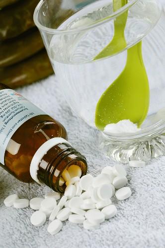Schüssler Salze in Tablettenform und aufgelöst im Wasserglas
