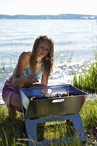 A young woman lighting a barbeque by a lake
