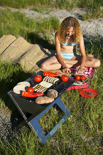 A young woman in a swimsuit having a barbeque