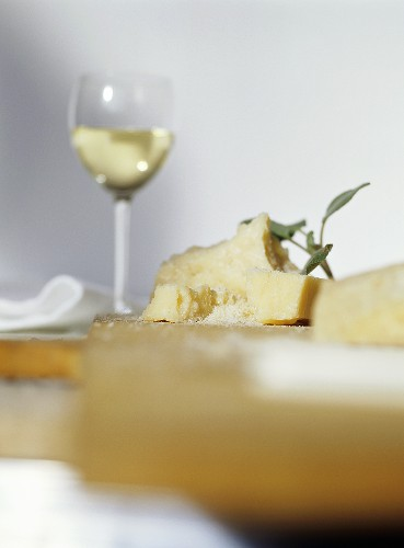 Pieces of Parmesan with sage and a glass of white wine