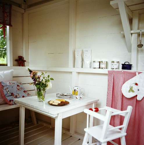 Table with child's tableware, biscuits and high chair