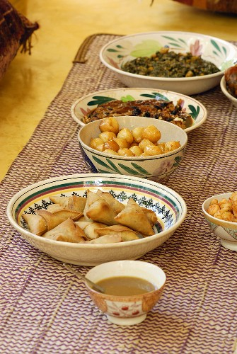 Several African foods in dishes on a carpet