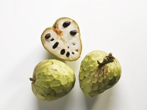 Cherimoyas, two whole and one halved