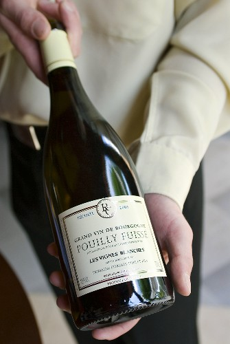 Man showing a labelled bottle of white wine