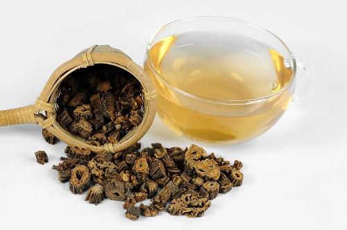 Pieces of dried gentian root with tea strainer and tea