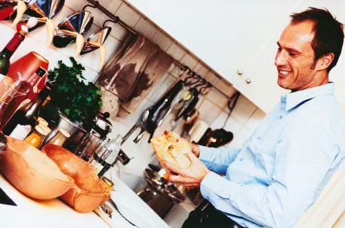 Man cooking chicken in terracotta pot (Romertopf)